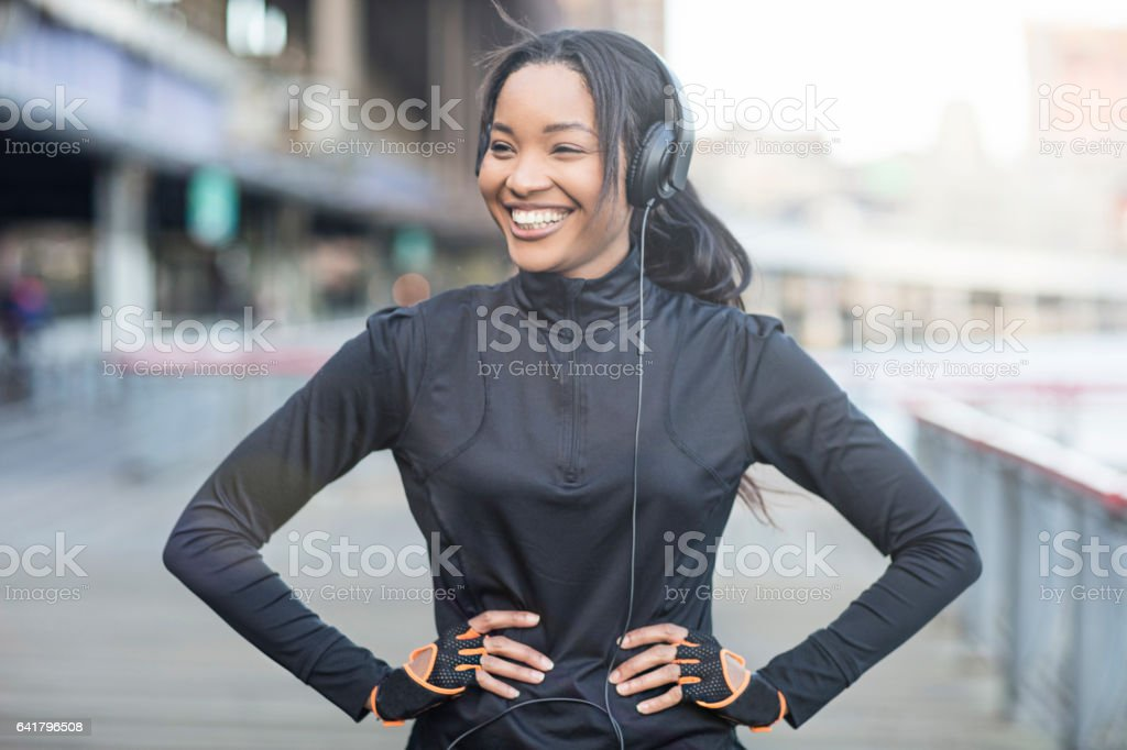 Cheerful athlete standing with hand on hip in city stock photo