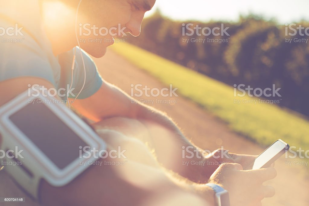 Cheerful athlete using smartphone in the park stock photo