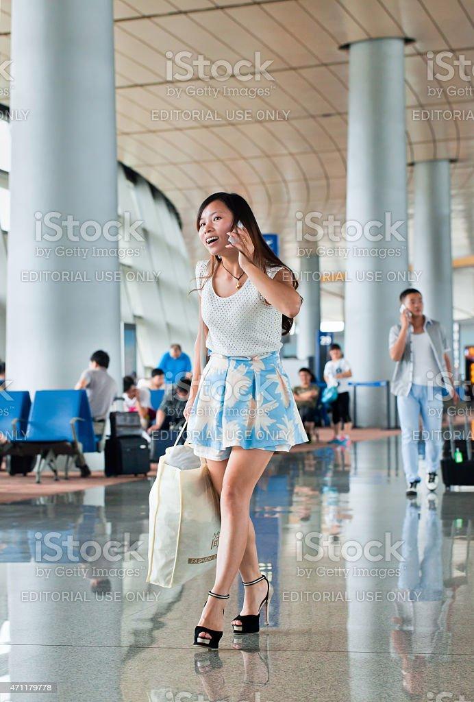 Cheerful, attractive girl makes phone call at Kunming Changshui Airport. stock photo