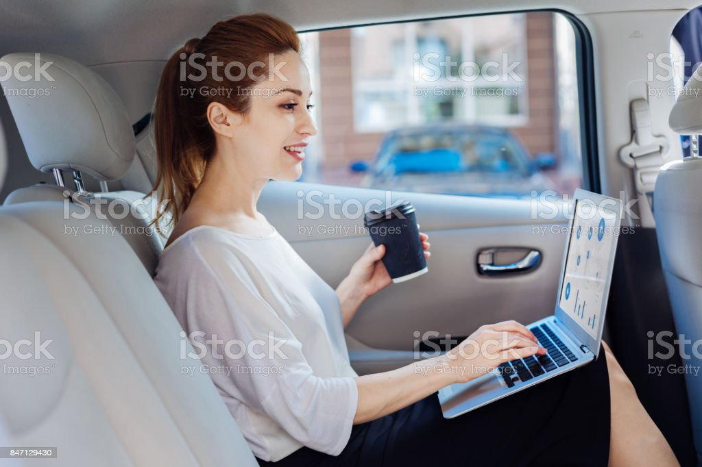 Cheerful attractive woman looking at the laptop screen stock photo