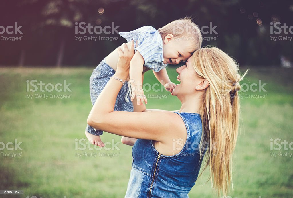 Cheerful aunt playing with her baby boy outdoors stock photo