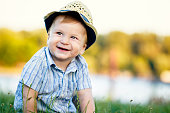 Cheerful baby boy with a hat in nature