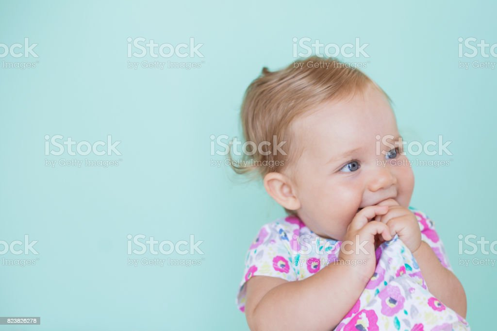 A cheerful baby with her hand and dress in her mouth stock photo