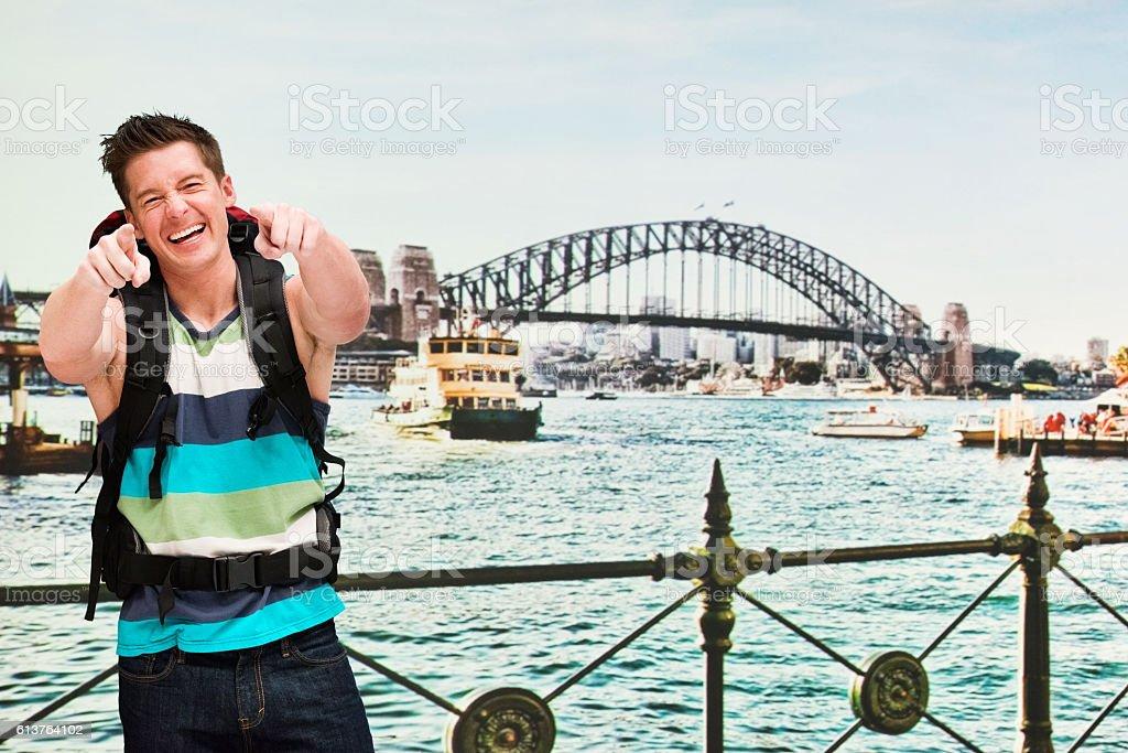 Cheerful backpacker pointing at camera stock photo