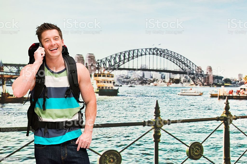 Cheerful backpacker talking on phone outdoors stock photo