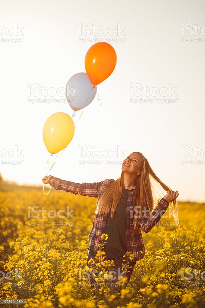 Cheerful beautiful woman with balloons in nature stock photo