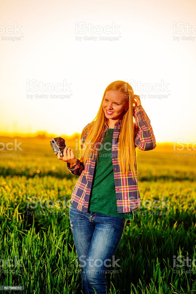 Cheerful beautiful woman with camera shootingsunset stock photo