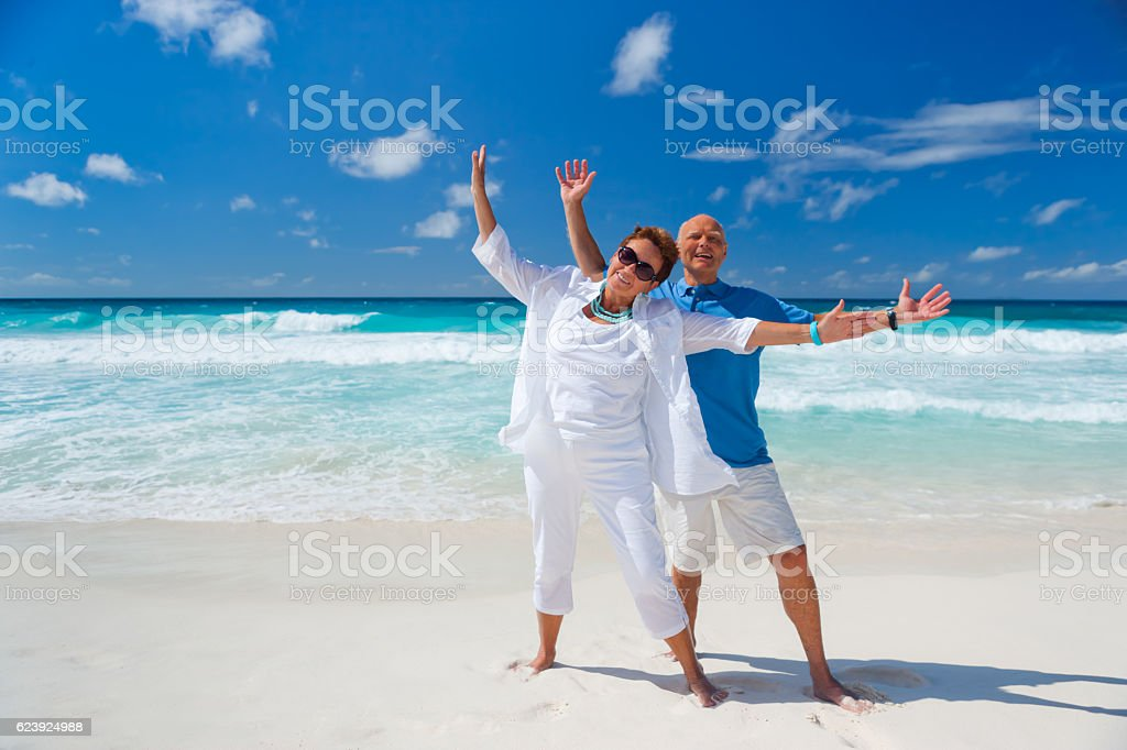 cheerful best ager couple on sandy beach stock photo