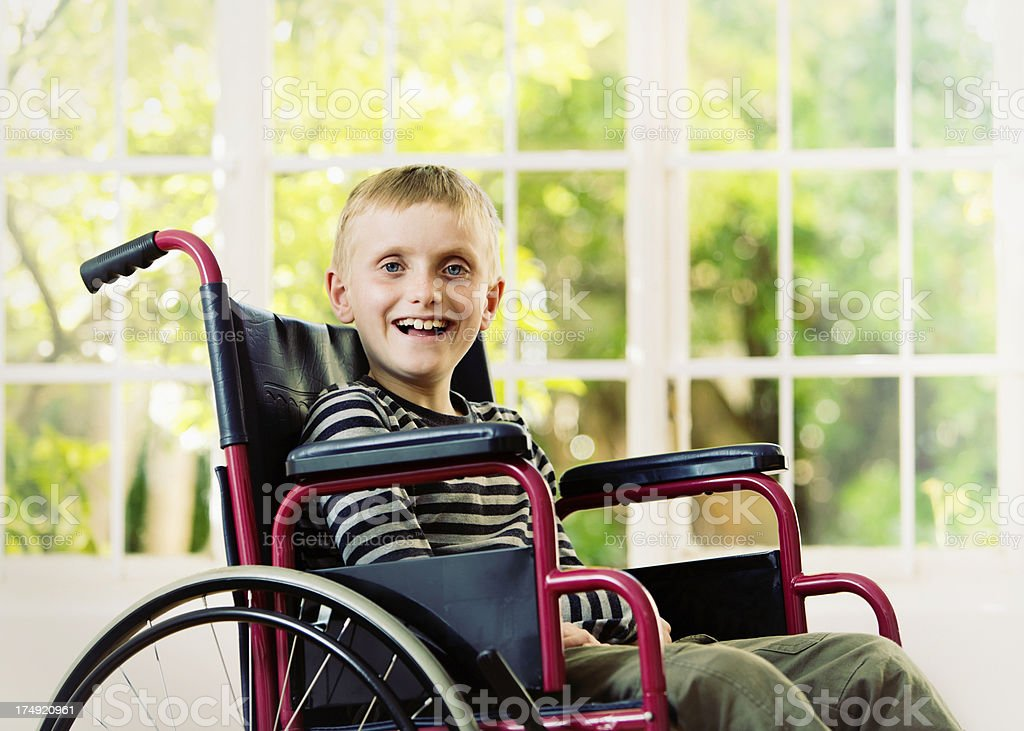 Cheerful blond schoolboy in wheelchair smiles confidently stock photo