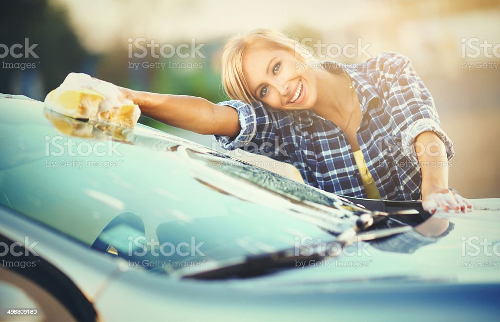 Cheerful blond woman washing her car. stock photo