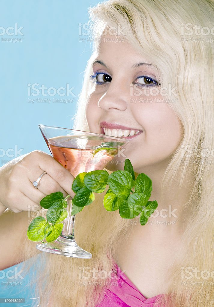 Cheerful blonde holds in hand glass and  mint royalty-free stock photo