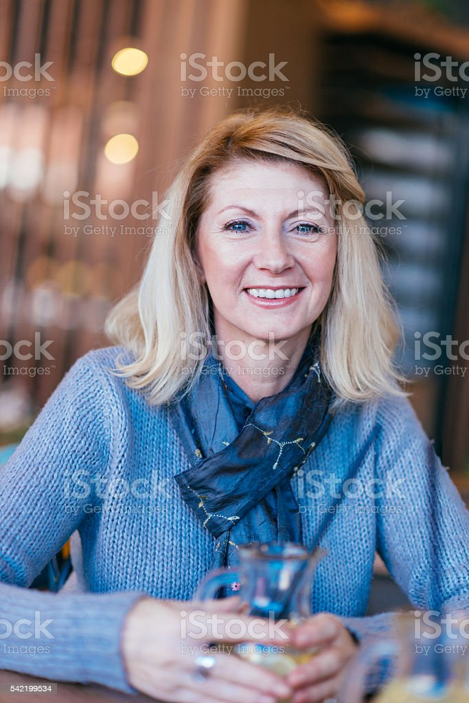 Cheerful blonde mature woman smiling stock photo