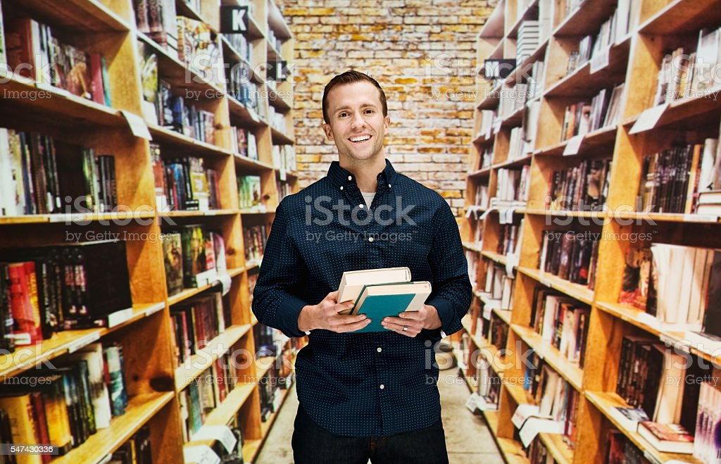 Cheerful bookseller standing in library stock photo