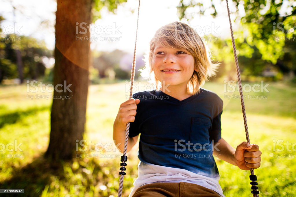 Cheerful boy playing on swing in park at sunset stock photo