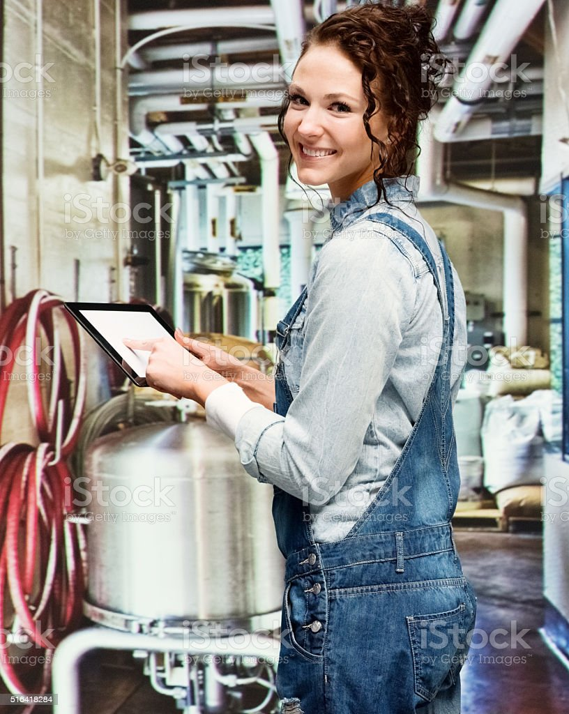 Cheerful brewmaster using tablet in brewery stock photo