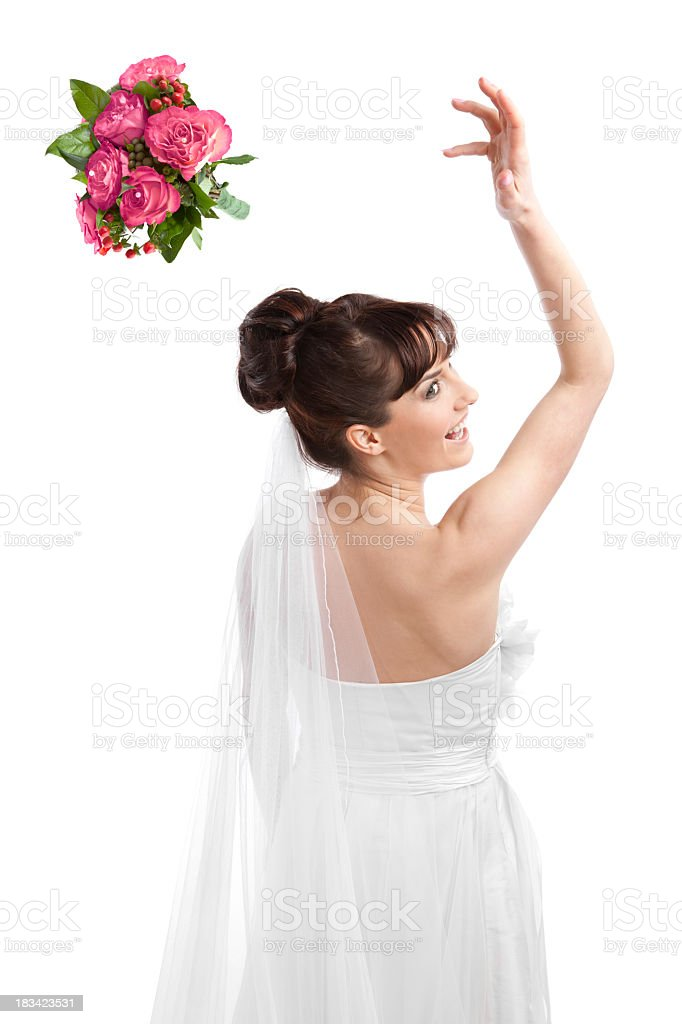 Cheerful bride throwing her bouquet of flowers stock photo