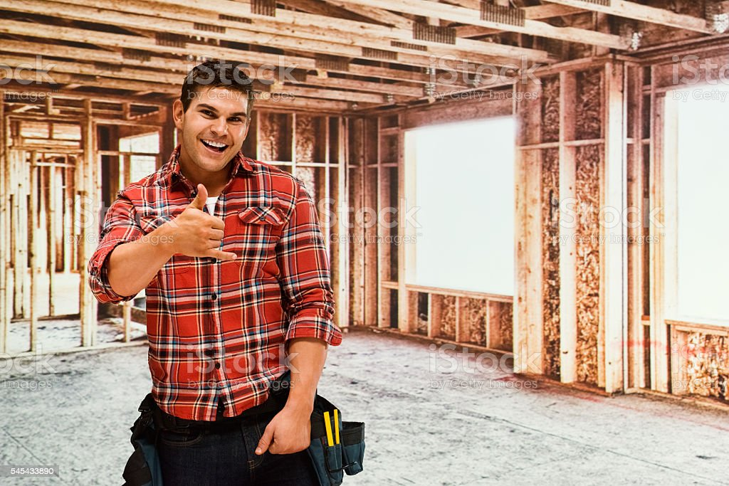 Cheerful building contractor giving shaka sign stock photo
