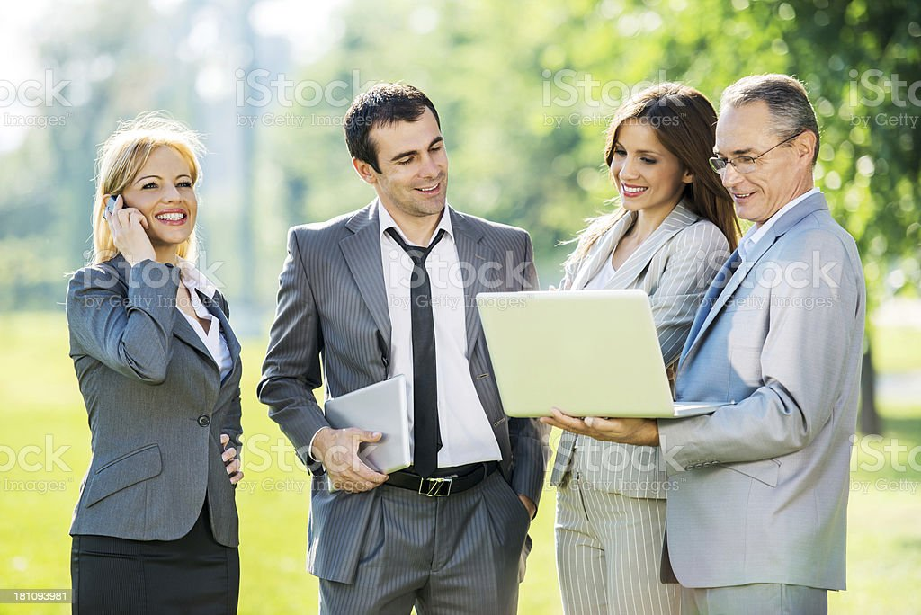 Cheerful business people using wireless technology outdoors. royalty-free stock photo