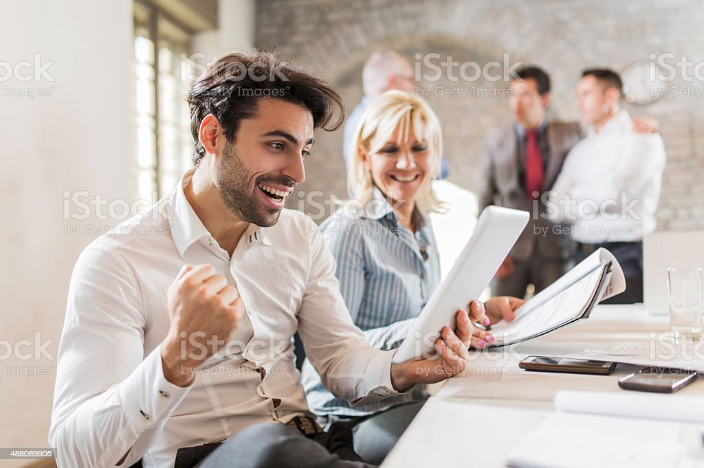 Cheerful businessman celebrating his business success in the office. stock photo