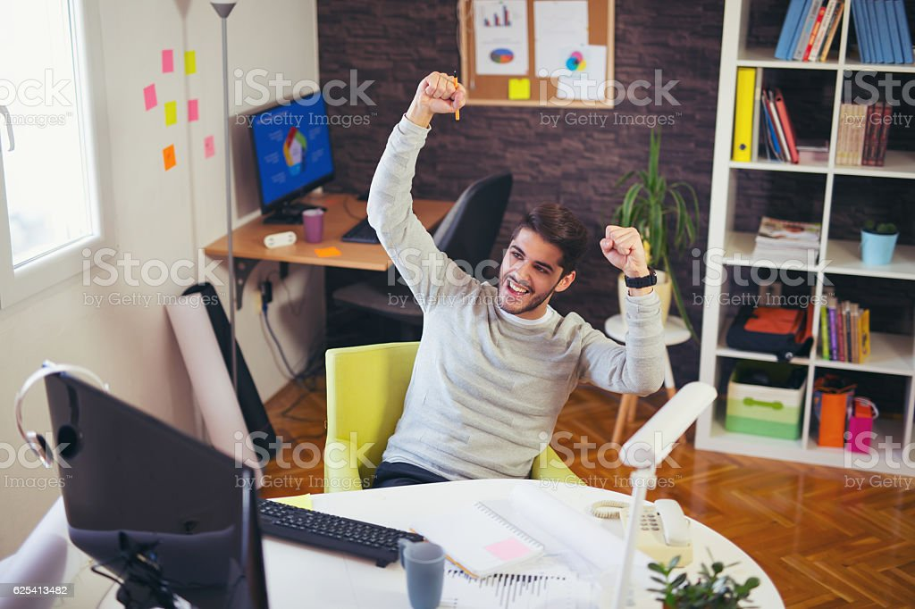Cheerful businessman cheering in the office stock photo