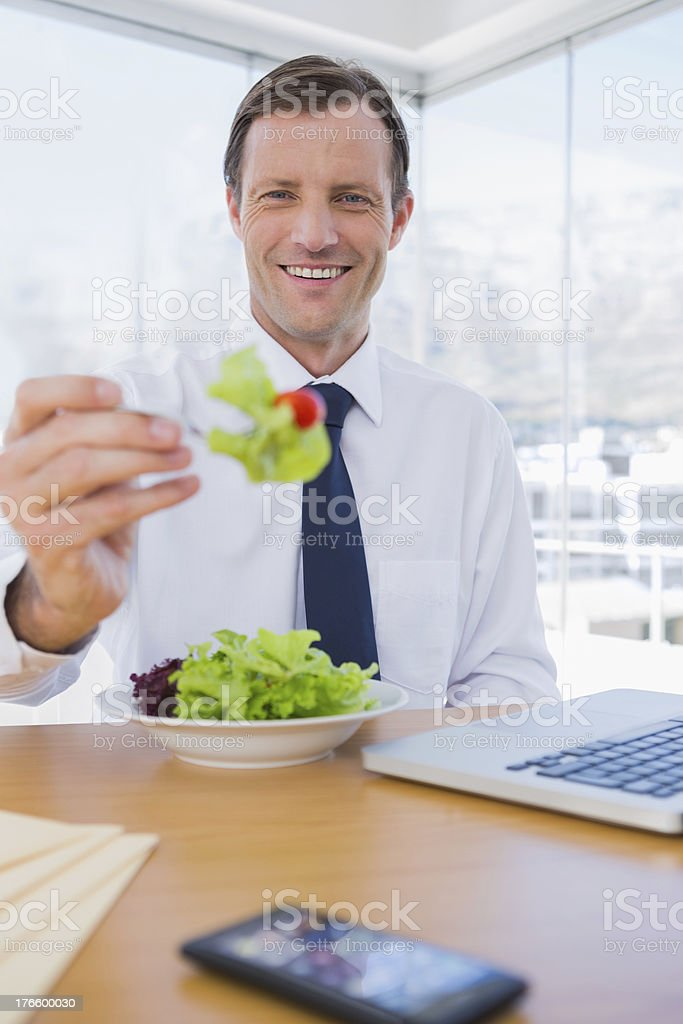 Cheerful businessman eating a salad royalty-free stock photo