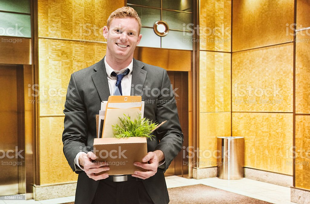 Cheerful businessman holding box stock photo