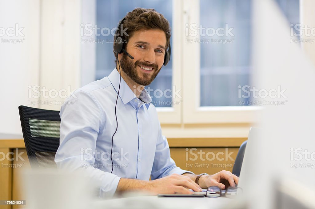 Cheerful businessman in the office on the phone, headset, Skype stock photo