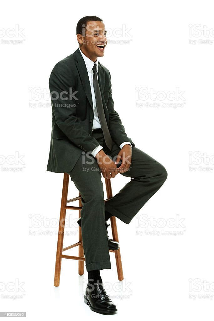 Cheerful businessman on stool and looking away stock photo
