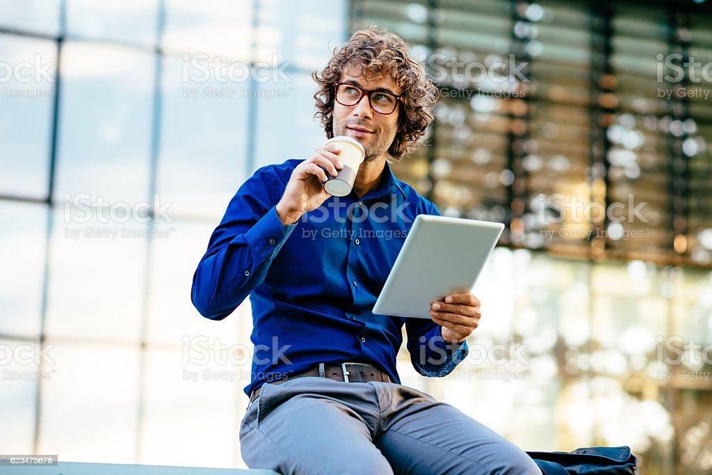 Cheerful businessman reading news on digital tablet stock photo