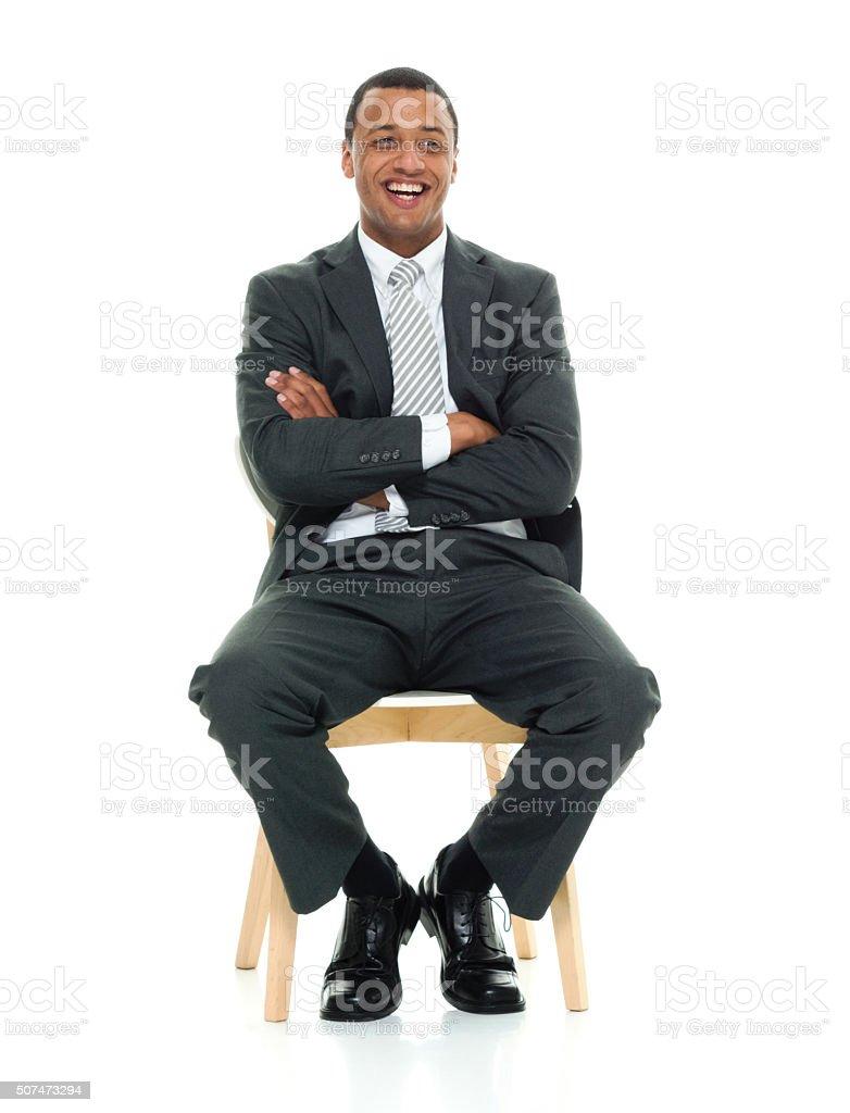 Cheerful businessman sitting on chair stock photo