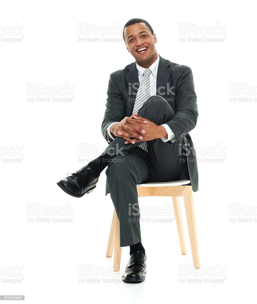 Cheerful businessman sitting on stool stock photo
