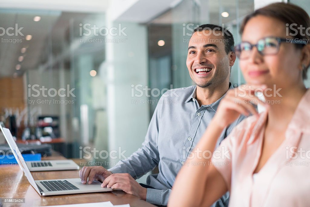 Cheerful businessman using laptop in board room stock photo