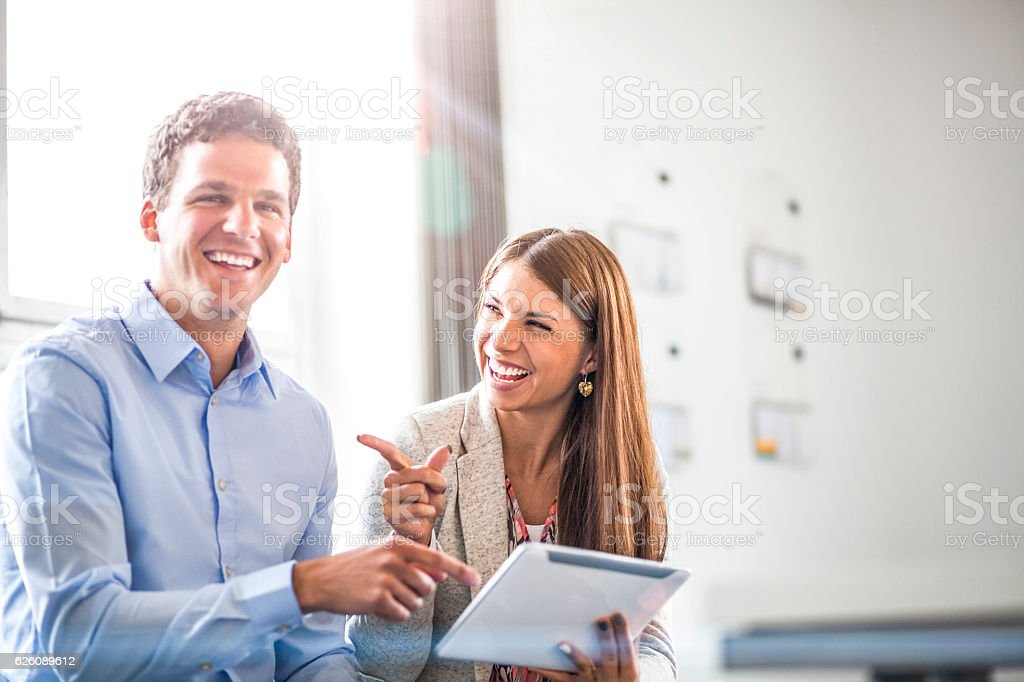 Cheerful businessman with female colleague using digital tablet in office stock photo