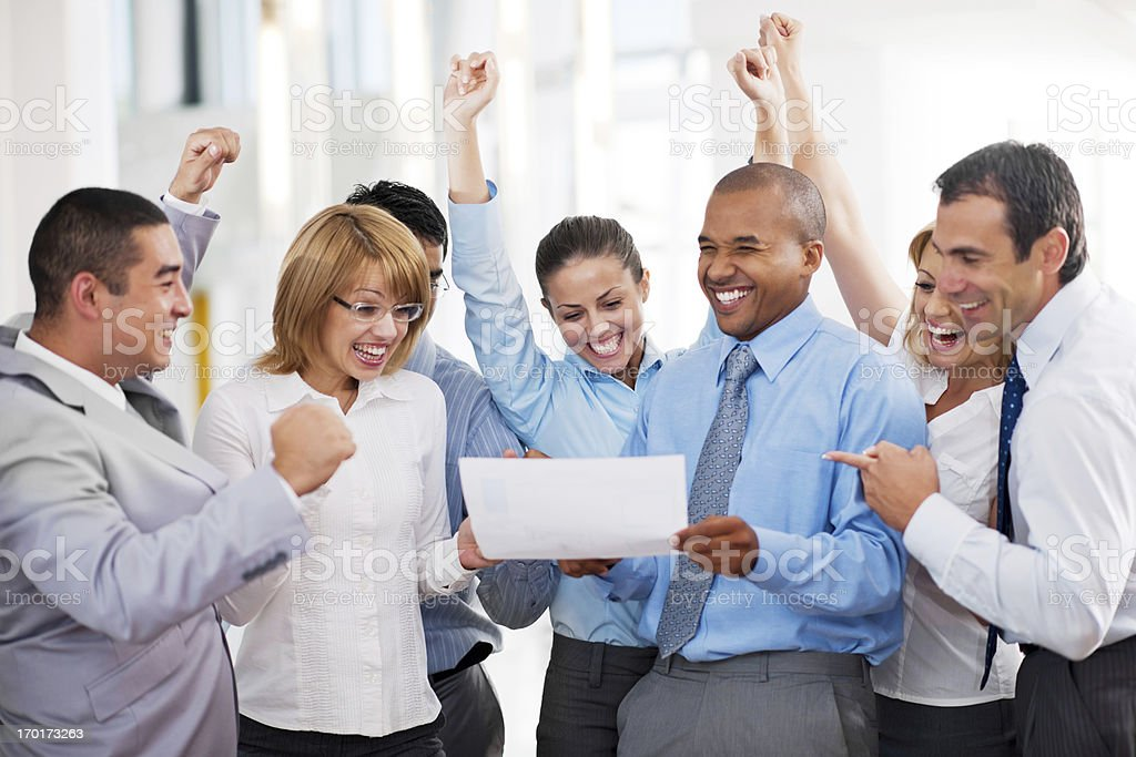 Cheerful businesspeople looking at the report. stock photo