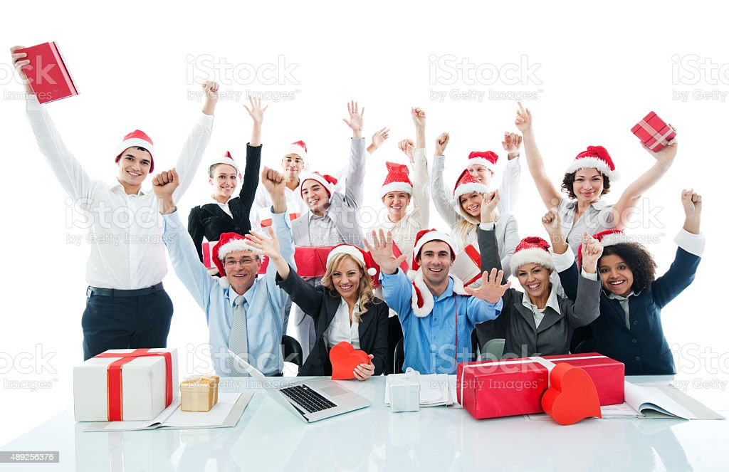 Cheerful businesspeople wearing Santa's hats and looking at camera. stock photo