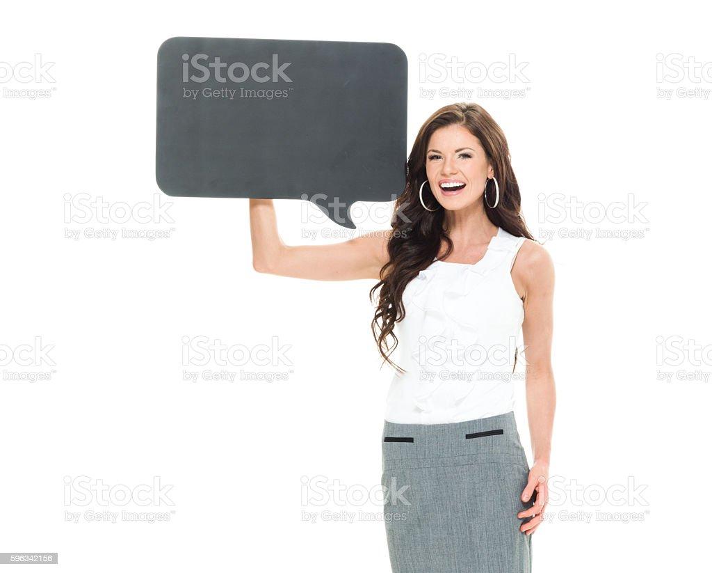 Cheerful businesswoman holding speech bubble stock photo