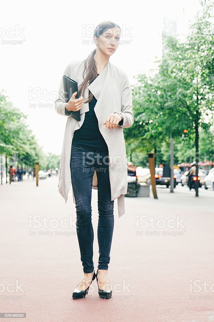 Cheerful Businesswoman In Urban Landscape Looking For A Taxi stock photo