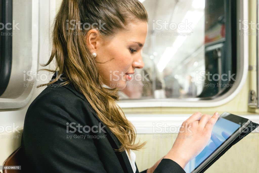 Cheerful Businesswoman On Subway Train Using Digital Tablet stock photo
