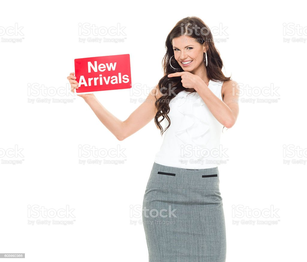 Cheerful businesswoman pointing at new arrivals sign stock photo