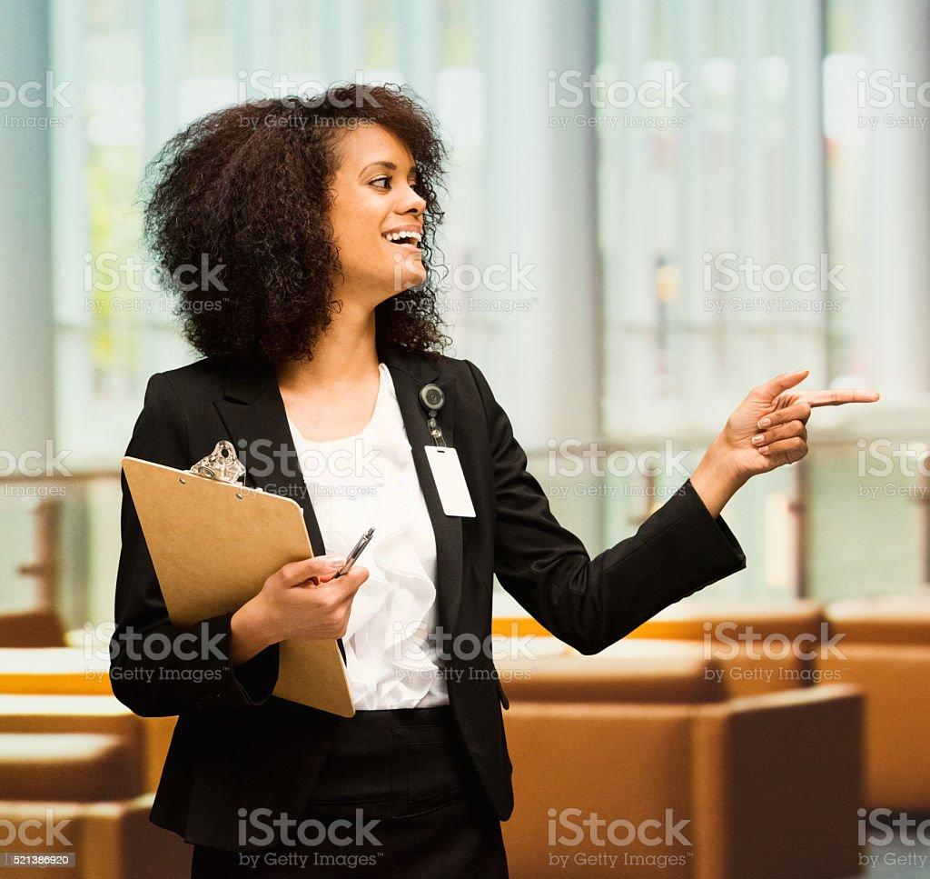 Cheerful businesswoman pointing away stock photo