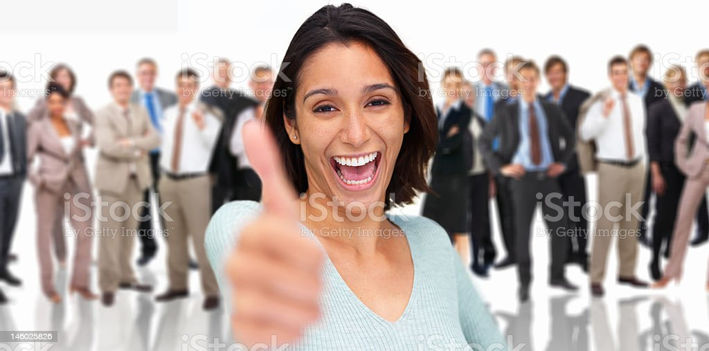 Cheerful businesswoman showing thumbs up with colleagues standing behind her royalty-free stock photo