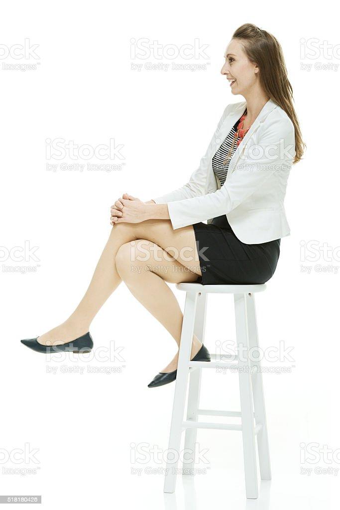 Cheerful businesswoman sitting on stool stock photo