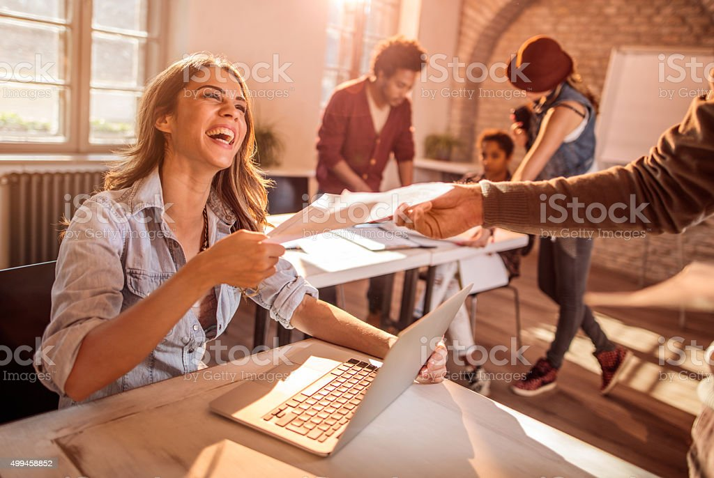 Cheerful businesswoman taking paperwork from her colleague in the office. stock photo
