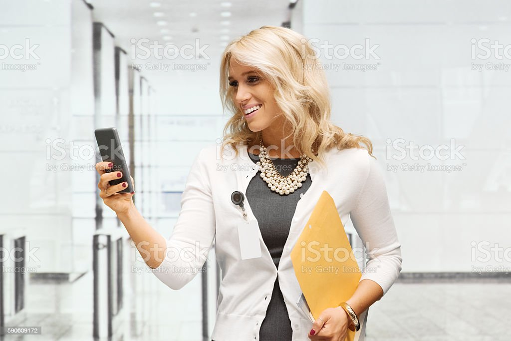 Cheerful businesswoman using phone stock photo