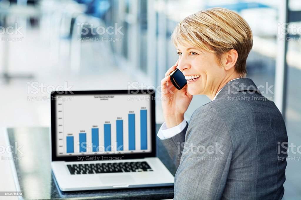 Cheerful businesswoman with laptop and cell phone royalty-free stock photo