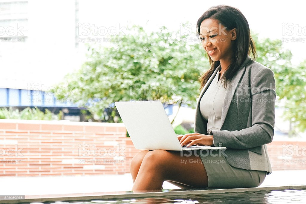 Cheerful Businesswoman Working With Laptop Outdoors stock photo