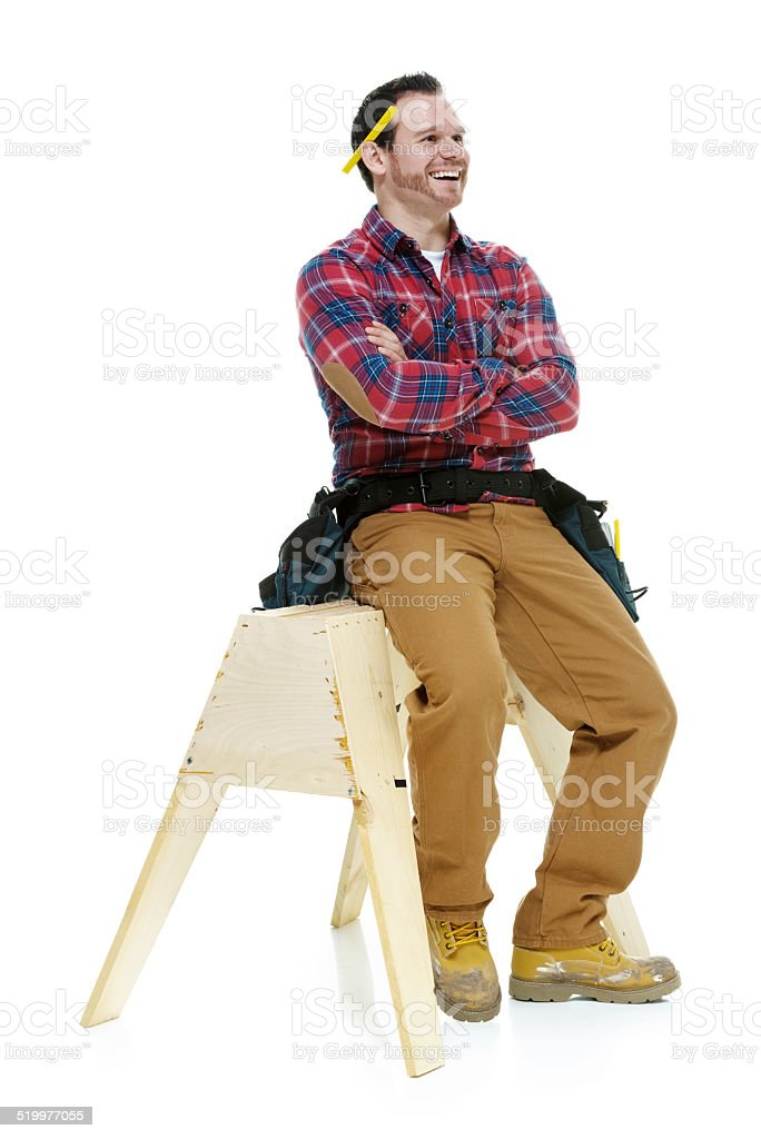Cheerful carpenter on sawhorse with arms crossed stock photo
