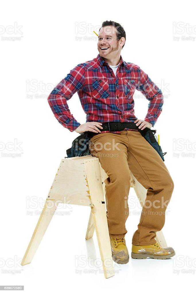 Cheerful carpenter sitting on sawhorse stock photo
