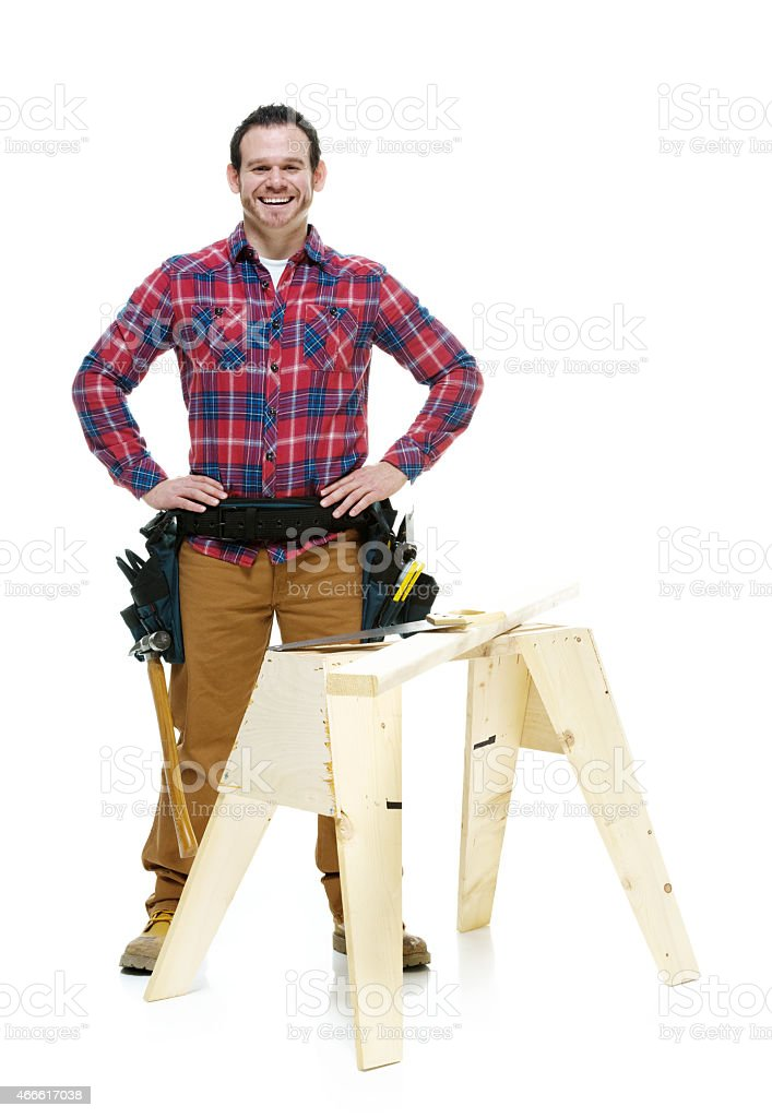 Cheerful carpenter standing and looking at camera stock photo