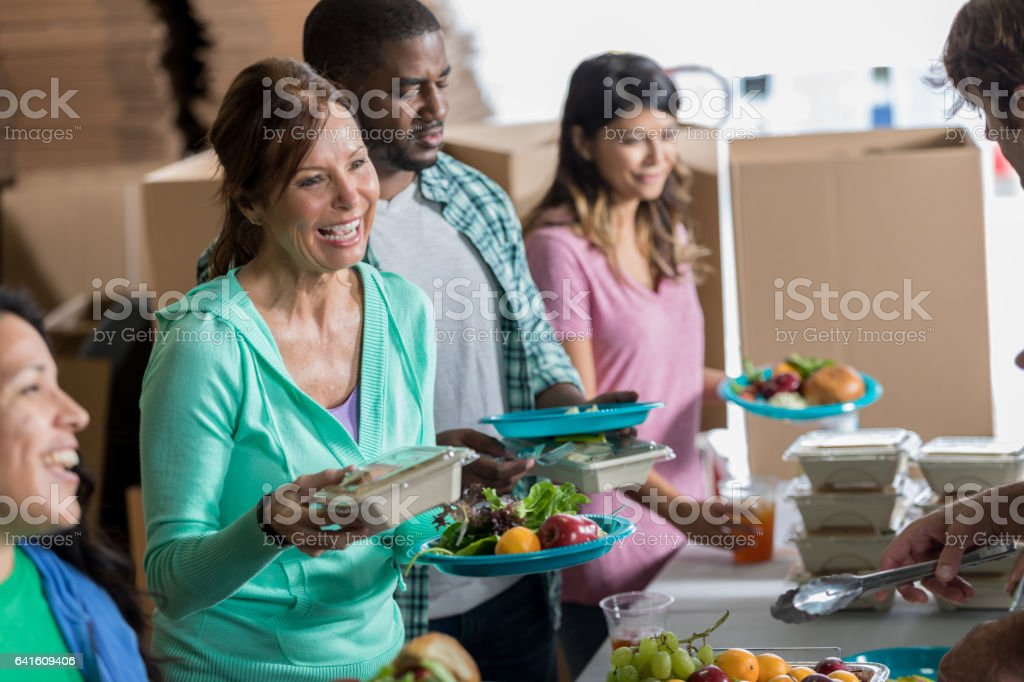 Cheerful Caucasian woman receives meal in soup kitchen stock photo